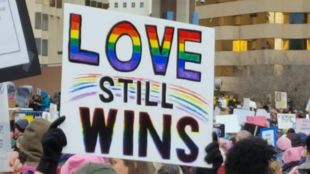 "Protest sign reading ""Love Still Wins"""