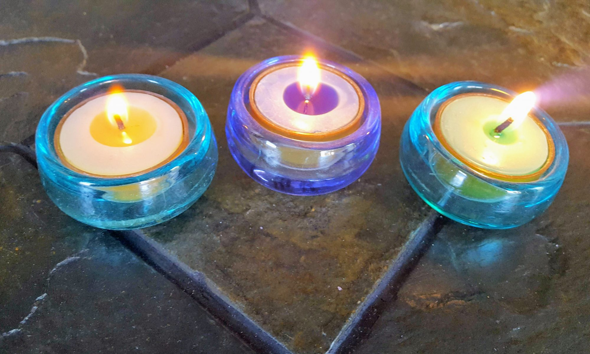 Photo of three small lit tea candles, but we are not talking about the Trinity.