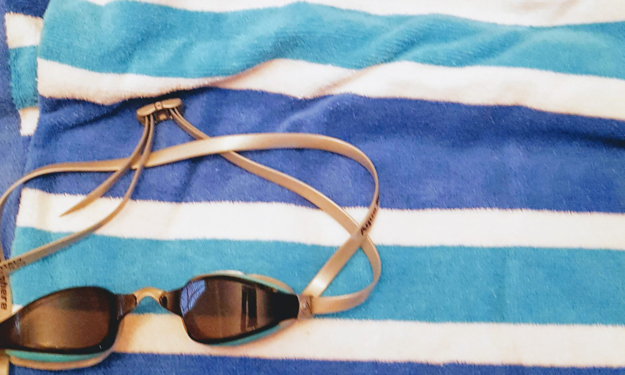 Photo of striped beach towel and swim goggles